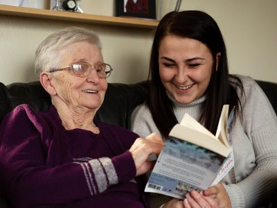 Carer and Client reading a book   Bridgewater Home Care